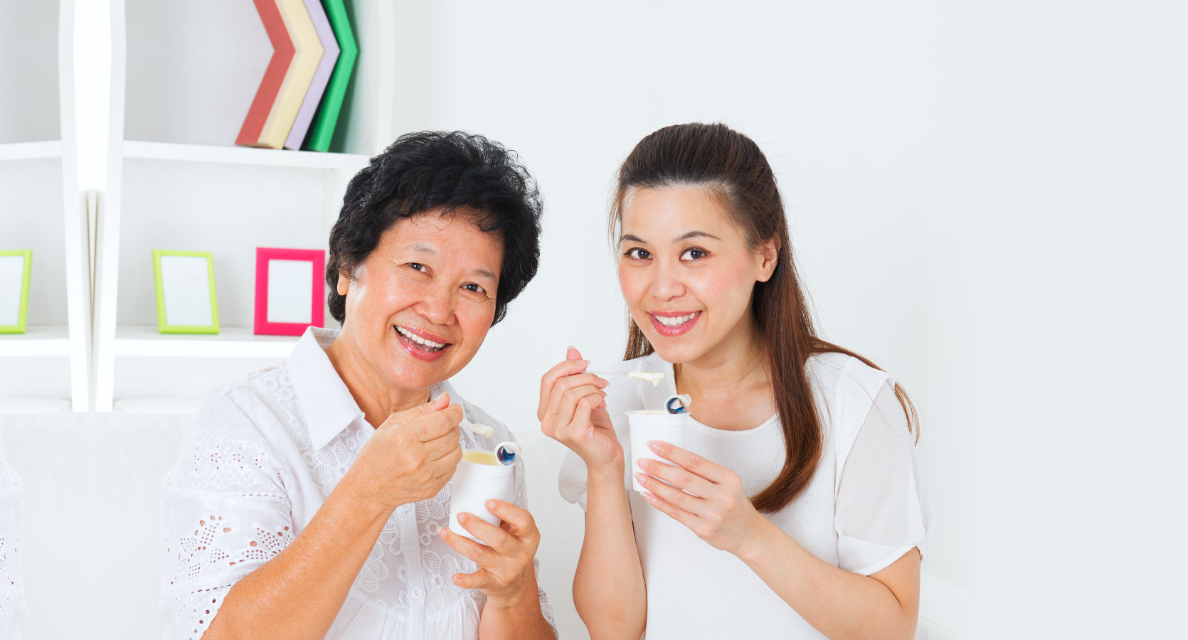 mother and daughter happily eating yogurt