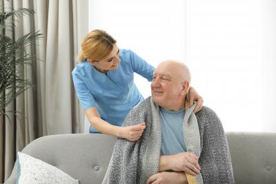 caregiver putting a blanket on a senior man
