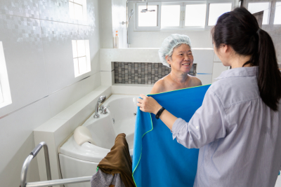 caregiver helping a senior woman take a bath