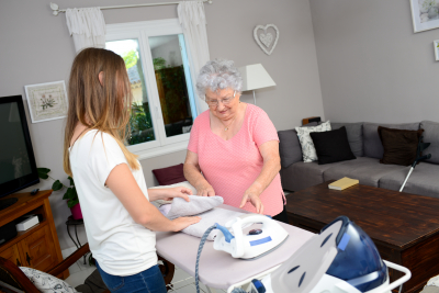 caregiver assisting a senior woman in ironing and folding
