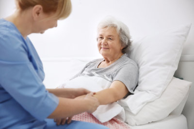 Caregiver massaging hand of senior woman at home